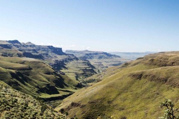 Utsikten från Drakensbergen i KwaZulu-Natal i Sydafrika, det är många kullar med grönt gräs i en nästan oändlig vy.