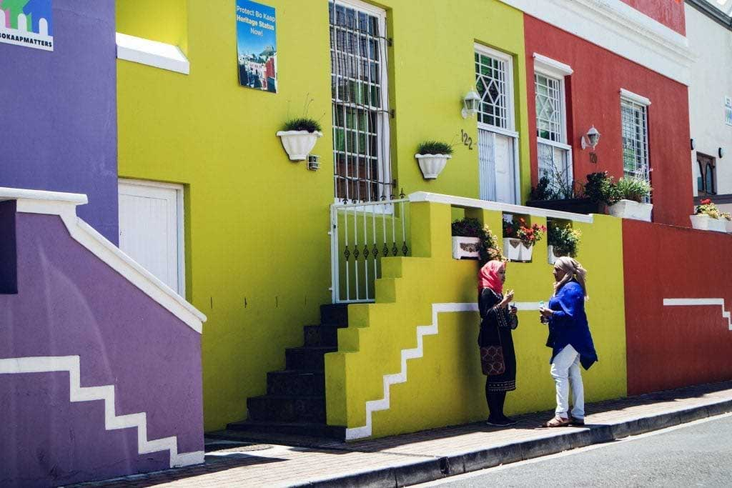 två kvinnor pratar framför färgglada hus i bo kaap, Kapstaden