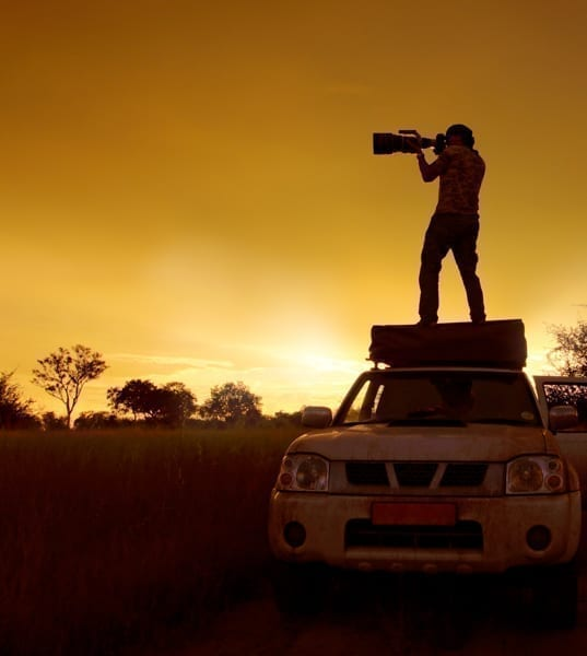 Siluett av en fotograf som står på en safaribil och fotograferar medan solen går ner i bakgrunden. Kameran är en av 5 saker jag alltid packar när jag är ute och reser.