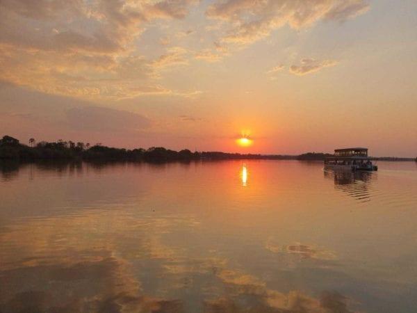Solen går ner och reflekteras brandgult i Zambezifloden. Du kan göra den här typen av utflykt när som helst, det påverkar inte alls när det är bäst att besöka Victoriafallen