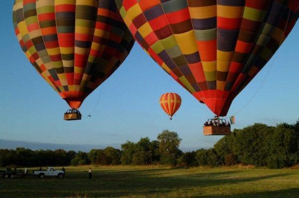 Tre luftballonger svävar över en safaribil. Bill Harrops Balloon Safaris tar dig från Johannesburg och Pretoria till en luftfärd du sent kommer att glömma