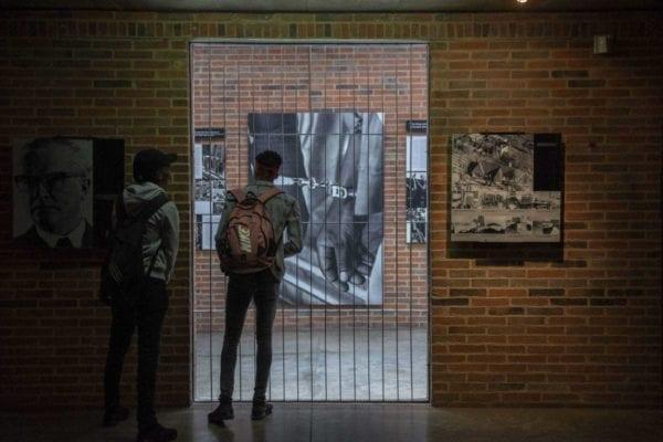 Två personer med ryggsäck tittar genom en grind på svartvita bilder på Apartheidmuseum, Johannesburg, Gauteng