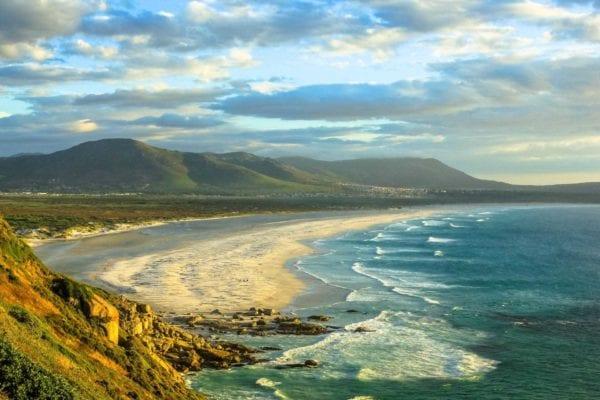 En lång strand sträcker sig över bilden som är mestadels blå med härligt hav och karaktärsfylld himmel. Just nu är det rea på resor till Afrika