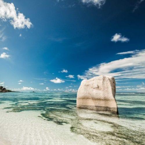 En sten sticker upp ur havet på en strand. Seychellerna öppnar för internationella turister