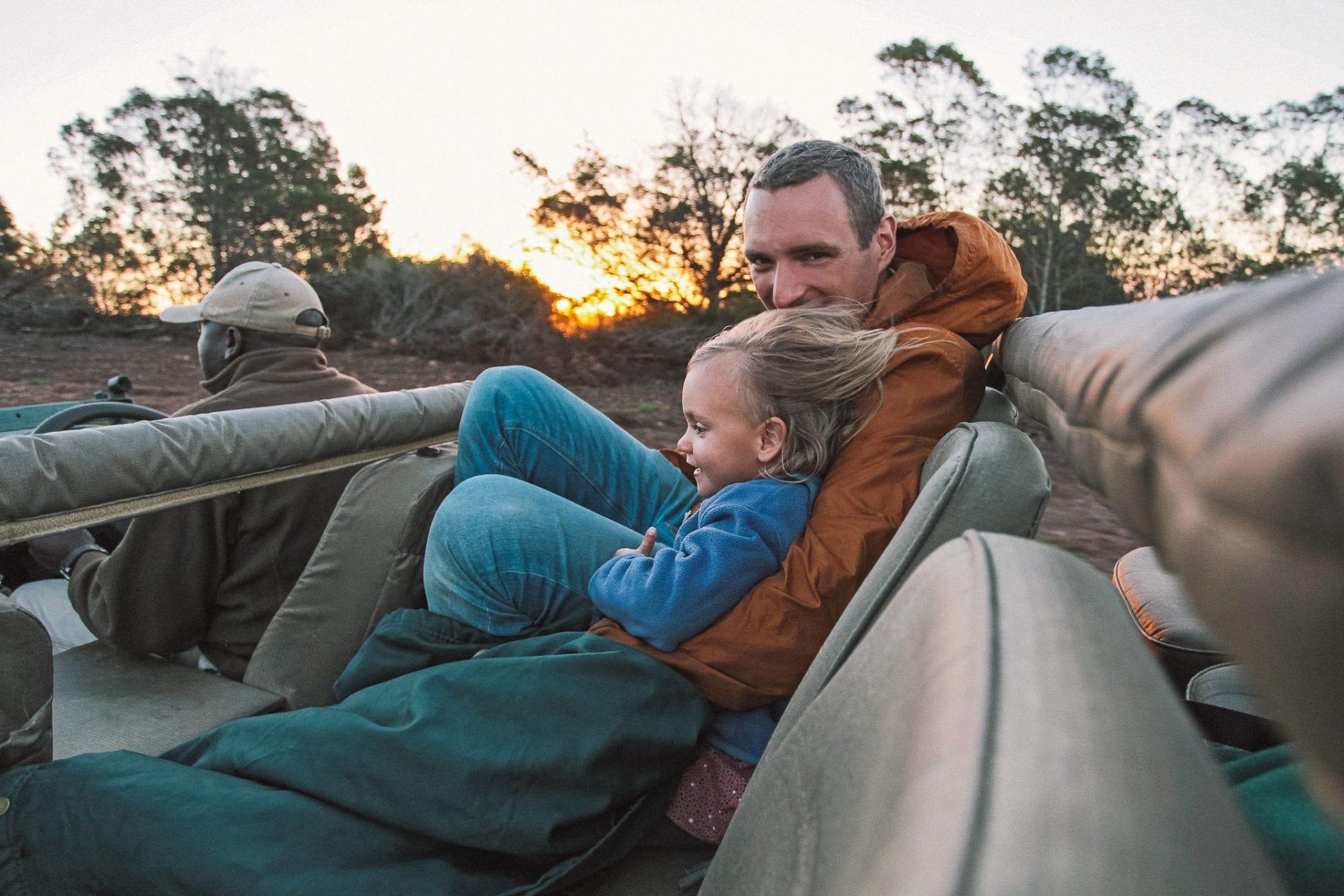 Pappa och barn i safaribilen. Klart du kan ta med dig barn på safari i Sydafrika