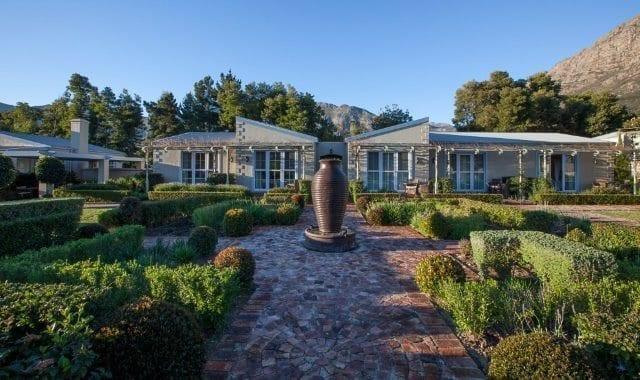 Trädgården på La Cabrière. En fin gångväg omgiven av buskage, med boendet i bakgrunden. Blå himmel.