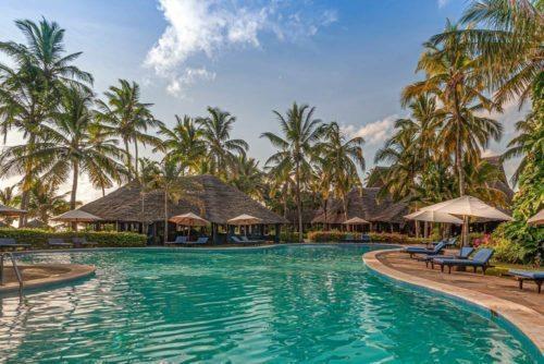 En grönskimrande pool med palmer mot en blå himmel, och solstolar och parasoller runt om poolen.