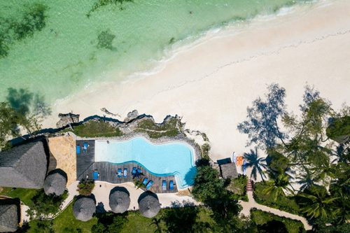 Pongwe Beach hotel ligger på en av de bästa stränderna på Zanzibar. Bilden visar hotellets infinitypool från ovan, och de omkringliggande solstolarna, baren samt havet.