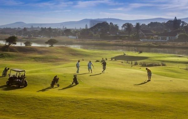 Några golfare spelar på en golfbana i Kapstaden. I bakgrunden syns vatten och ännu mer i bakgrunden några berg. Afrikakompaniet kan ordna din golfresa.