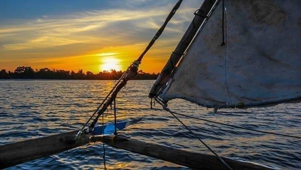 en solnedgångsseglats i Zanzibar, seglet på farkosten framför solnedgången.