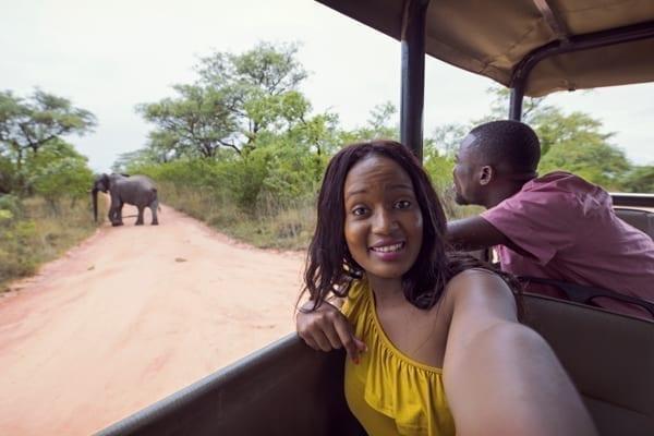 Två personer på safari i Afrika, i bakgrunden syns en elefant