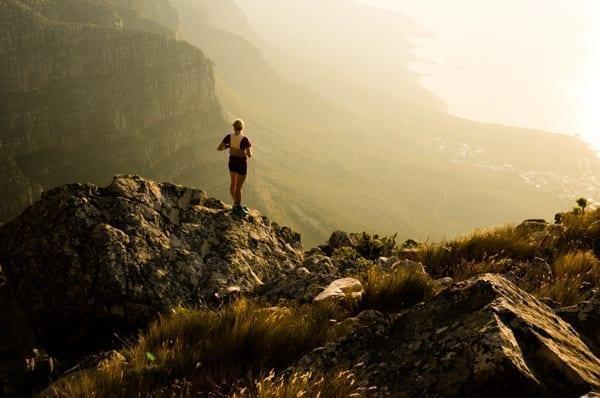Siluetten av en person med liten ryggsäck som ser ut över en häftig dal. Personen är uppe på en höjd.