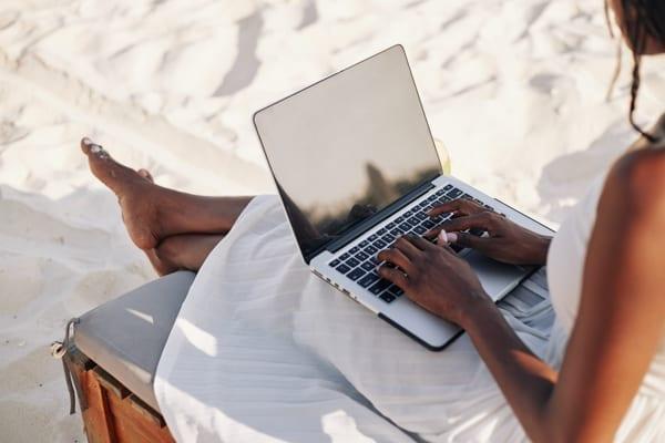 En kvinna sitter på en solstol på stranden med en laptop i knät.