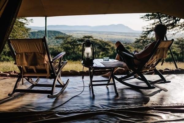 En man lutar sig tillbaka i sitt tält och tittar på utsikten, ett vilt savannlandskap i Masai Mara. På bordet finns en oljelampa. Cottars Safari Camp i Masai Mara i Kenya är att lyxa till semestern i kvadrat, här finns allt du kan önska dig.
