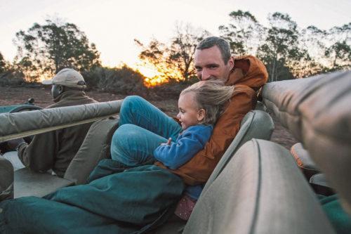 Just nu är det rea på resor till Afrika, bland annat på safariresor för familjer. Ett blont barn sitter med sin pappa i en safaribil, det är solnedgång