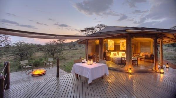 Just nu är det rea på resor till Afrika och lyxiga Leopard Hill har bra rabatter. På bilden ser du ett upplyst safaritält med dubbelsäng och härlig, färgglad inredning, runtomkring är det bush i solnedgången.