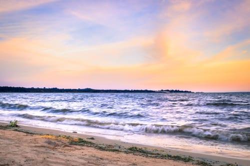 solen sjunker ner över Victoriasjön i Uganda, startpunkten för din resa där du kan möta bergsgorillor i Uganda