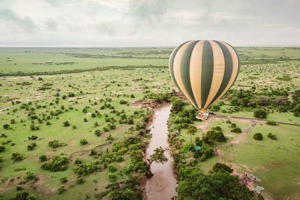 En varmluftsballong flyger över en flod i Maasai Mara National Reserve i Kenya. En fulländad höjdpunkt på din bröllopsresa i Afrika
