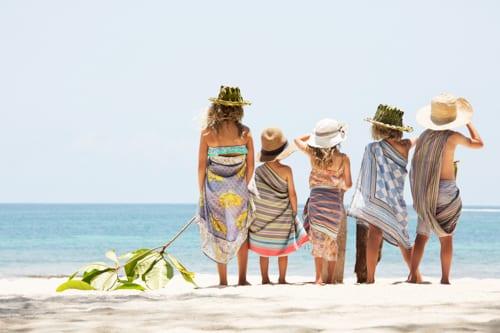 fyra barn och en vuxen står på stranden, med ryggarna mot oss. De är på Diani Beach i Kenya. I bakgrunden syns havet.