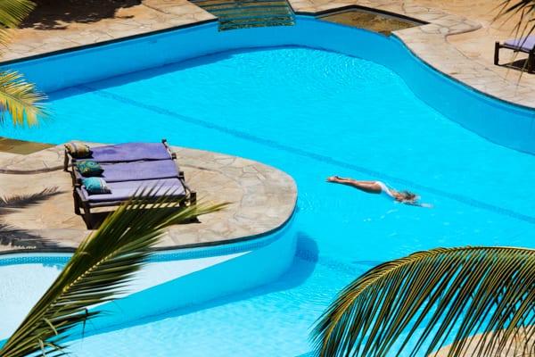 en kvinna simmar i en pool, det är några solstolar intill poolen men i övrigt är det tomt, bara vajande palmer. Kindondo Kwetu är en perfekt destination för dig som vill ha en romantisk bröllopsresa i Afrika