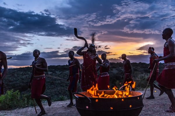 masai-dansare dansar runt en eld i den mörka kenyanska skymningen. En maasai blessing ingår i smekmånadserbjudandet för dig som vill åka på bröllopsresa i Afrika