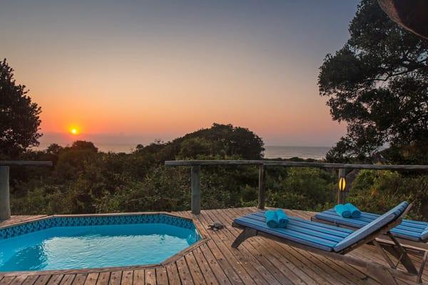 Två däckstolar bredvid en liten pool med utsikt över havet, solen går ner i horisonten. Utsikten från Thonga Beach Lodges Deluxe Ocean View Honeymoon Suite passar perfekt för dig som vill på bröllopsresa i Afrika och Sydafrika.
