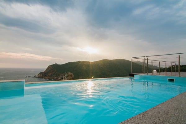 En turkos pool sträcker sig mot horisonten, där havet syns. Head over Hills i Knysna är en fantastisk destination för din bröllopsresa