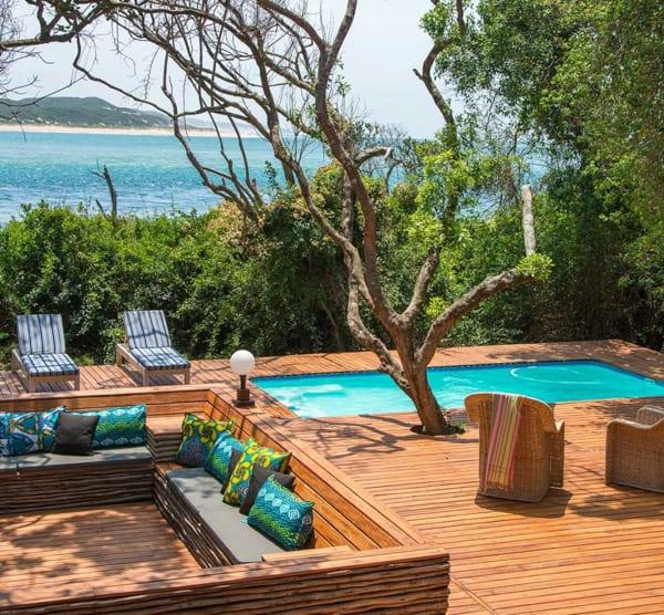 En färgglad uteplats med turkosa kuddar och en mindre pool med några solstolar. I bakgrunden syns havet. Machangulo Beach Lodge är en romantisk destination för din bröllopsresa i Afrika