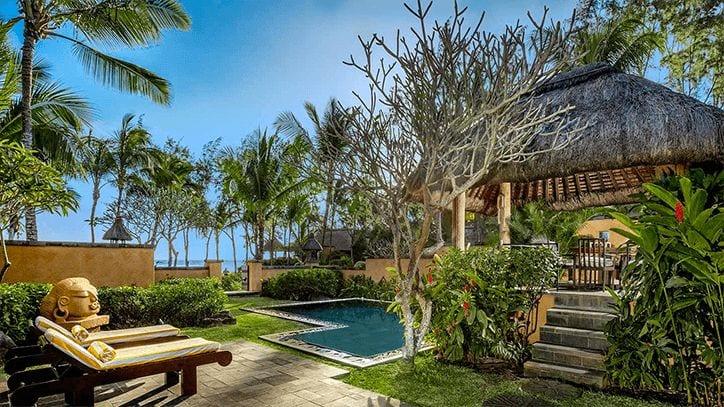 två solstolar intill en privat pool i en lummig trädgård bara några korta steg från stranden i Mauritius