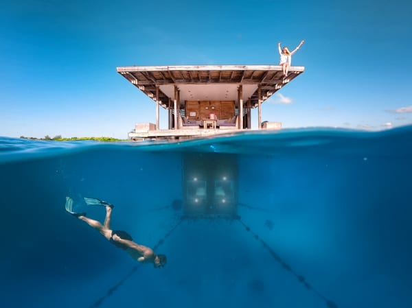 En person snorklar under vattennivån, i bakgrunden syns Manta Resorts Undervattensrum. På taket av den flytande trevåningsbyggnaden sitter en kvinna och ser glad ut. Åker du på bröllopsresa i Afrika ska du välja Manta resort på Pemba.