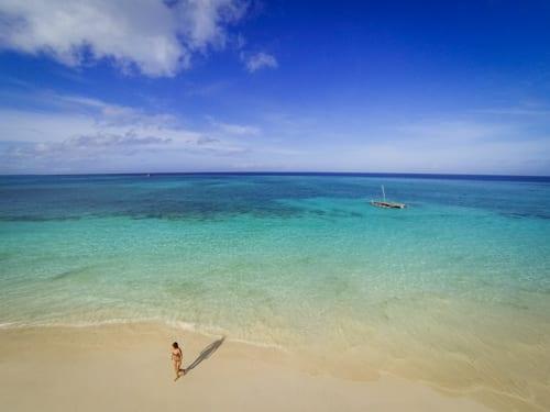 En ensam person står på en vacker, gyllene sandstrand med himmelsblått hav i bakgrunden och knappt ett moln på himlen. Resa till Afrika i covidtider kan innebära en helt underbar upplevelse.