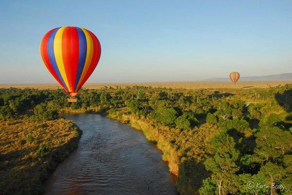 Två varmluftsballonger svävar över Marafloden i Maasai Mara, Kenya. Vare sig du väljer Tanzania eller Kenya för din safari kan du lägga till denna upplevelse.