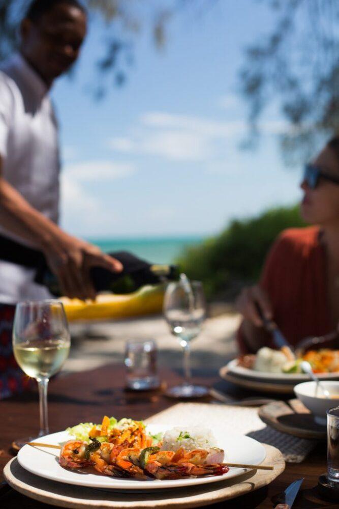Tanzania eller Kenya? Maten är snarlik men Tanzania är billigare. På bilden grillade räkor och vit vin som serveras en suddig person.