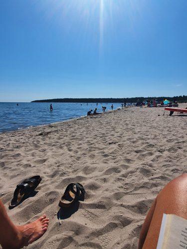 En strand, ett knä, fötter och ett par birkenstocks.